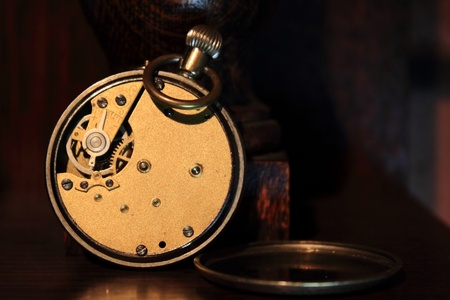 Pocket watch with the back plate removed revealing the mechanism. photo