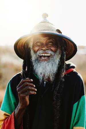 Portrait of old rastafari with dreadlocks smiling looking at the camera in the nature