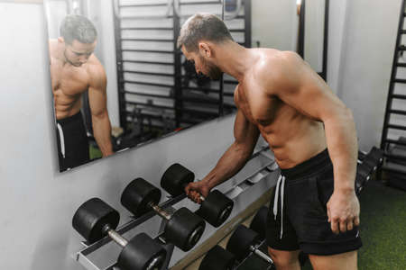 Men in the gym drinking water after exercising