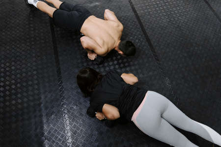 Friends doing pushups at the gym on black floor 版權商用圖片