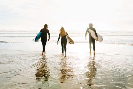 Three surfing friends entering the sea with surfboards in the morning