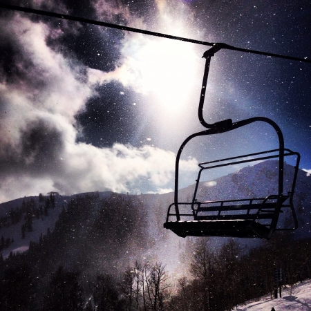 A chair lift in park city Utah with the sun reflecting off the clouds Фото со стока