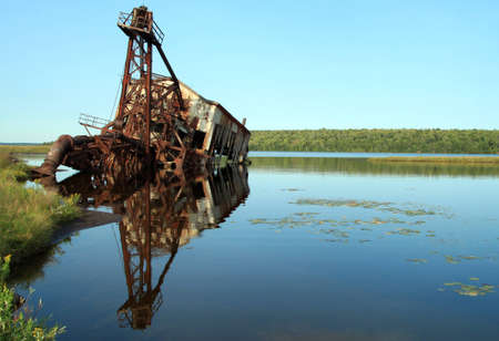 Perfect reflection of rugged machinery in calm bay photo
