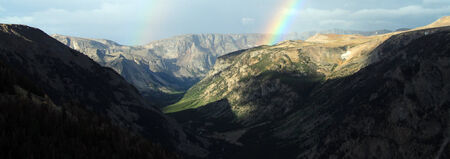 remoteness: Rainbow over a remote mountain range with steep valleys in a beautiful tranquil landscape, panoramic view Stock Photo