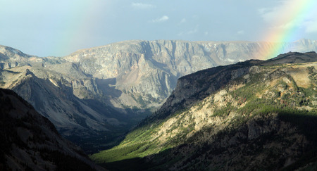 remoteness: Colourful rainbow in a mountainous landscape striking the top of a plateau above a steep mountain valley
