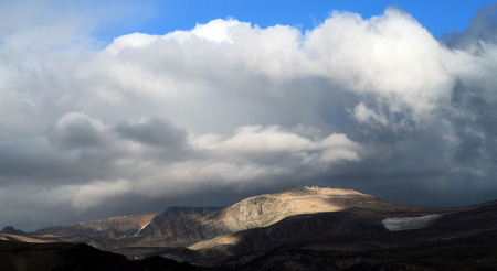 remoteness: Storm clouds gathering in a blue sky over a remote mountain range in a scenic landscape