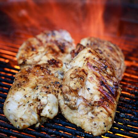 Four chicken breasts on charcoal grill with flame in the background