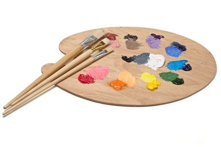 Artist s palette with paints and brushes photo