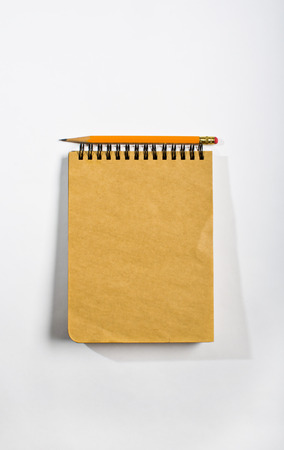 metal spring: paper notebook with a pencil and a metal spring Stock Photo