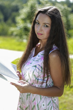 autodidact: Portrait of a pensive female student holding book and looking away outdoors