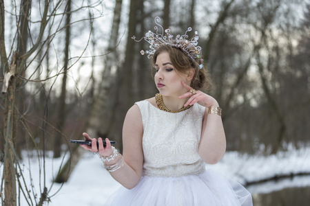winter photos: Beautiful girl Crown taking photos herself  the winter outdoors