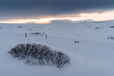 Beautiful sunset over the winter Iceland. Scandinavian landscape and gorgeous Icelandic scenery in the winter time. Tourism in Iceland leads you to visit this awesome place all years long.