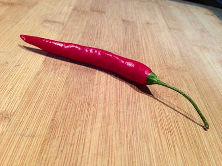 Single long red cayenne pepper with stalk on a bamboo cutting board