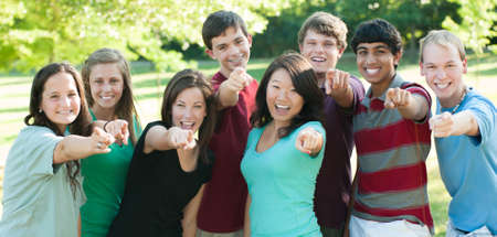 cultural diversity: Un grupo multi�tnico de adolescentes fuera de amigos se�alando Foto de archivo