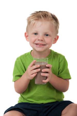 Jonge gelukkige jongen met chocolade melk in een groen shirt op een witte achtergrond Stockfoto