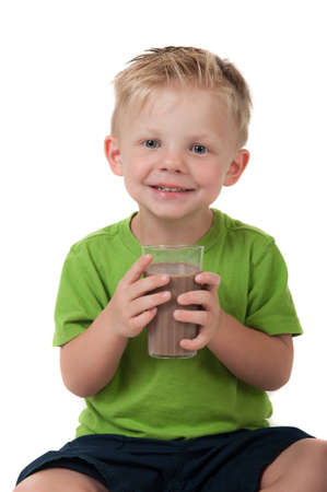 Young happy boy holding chocolate milk in a green shirt on a white background
