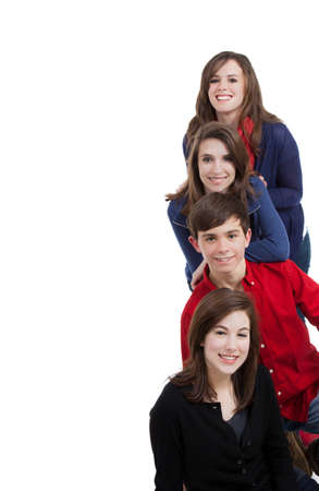 Four teenagers smiling on a white background with copy space