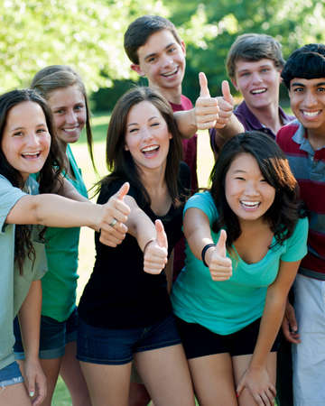 of cultural: A multi-ethnic group of teenage friends outside with thumbsup Stock Photo