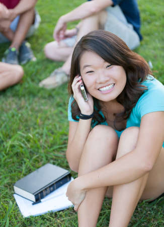 A young Asian girl talking on phone outside with friends in the background photo