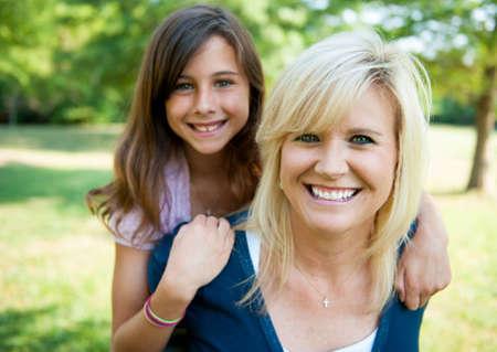 mere et fille: M�re avec sa jeune fille sur son dos en souriant Banque d'images