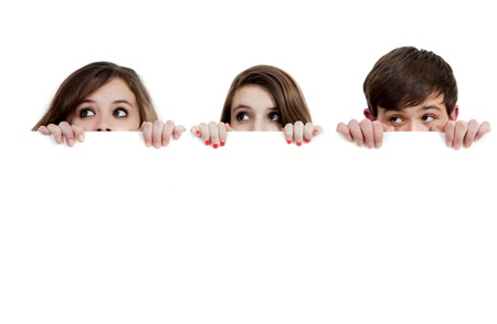 Three teenagers peeking over a white background with copy spcae Stock Photo