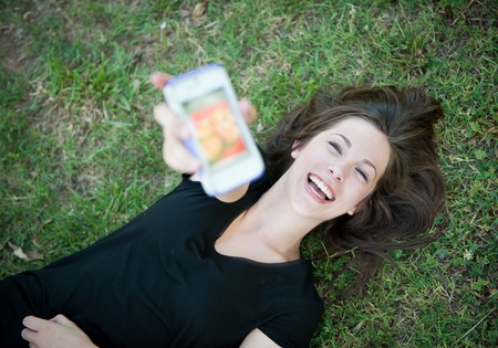 A young happy girl lying on the grass laughing at her phone Stock Photo