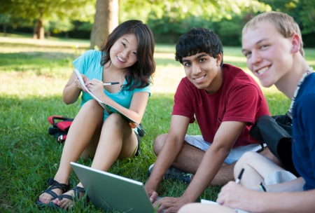 A group of three happy teenagers studying outside