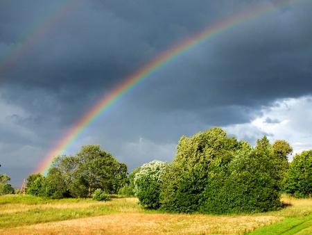 Rainbow in cloudy sky over rural landscape