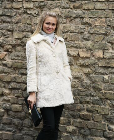 Young Pretty Woman In Fur Coat With Clutch Near Old Brick Wall