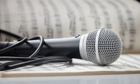 Microphone with cable lying on sheet music Stock Photo