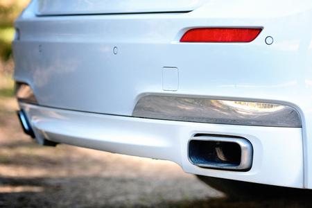 Messa a fuoco selettiva sul paraurti del tubo di scarico del sensore di parcheggio nella parte posteriore del paraurti bianco auto di lusso si chiuda su sfondo sfocato chiaro.