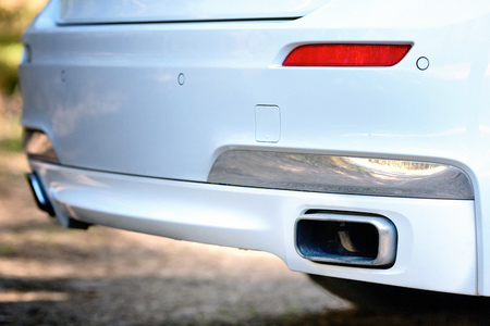 Selective focus on parking sensor exhaust pipe bumper at rear of white luxurious car bumper close up on light  blurred background.