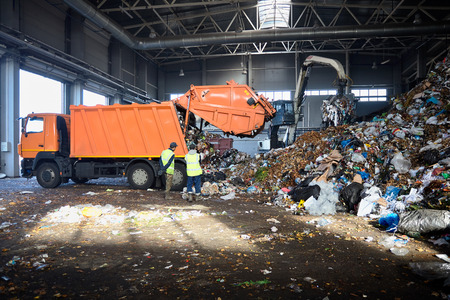 Two workers of recycling plant control process of unloading garbage from garbage truck. Manipulator loads garbage on conveyor for further processing and sorting. Stock Photo