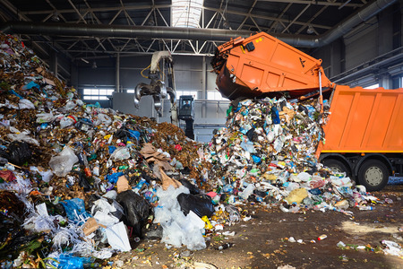 GRODNO, BELARUS - OCTOBER 2018: recycling plant process of unloading garbage from garbage truck. Manipulator loads garbage on conveyor for further processing and sorting. Editorial