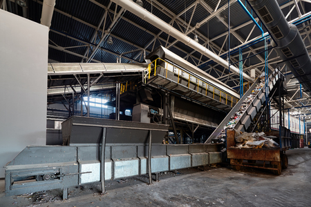 Conveyor belt at recycling plant transports garbage inside drum filter or rotating cylindrical sieve with trommel or screen for sorting pieces of garbage into fractions of various sizes.