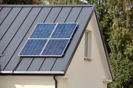 Solar panels installed and in use for renewable ecological clean green energy on dark metal roof of rural home.
