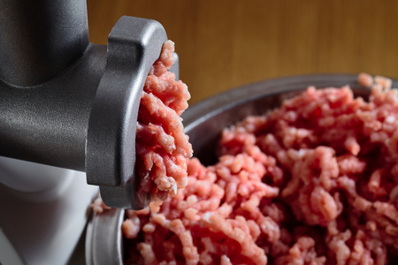 Minced fresh meat coming out from modern electric grinder on oak table as background. Healthy fresh homemade minced meat. Place for copyspace.