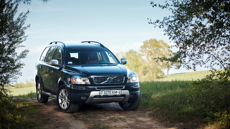 GRODNO, BELARUS - MAY 2015: Volvo XC90 4.4 v8 1st generation restyling 4WD SUV test drive in spring field country road on blur sky background in Grodno Belarus