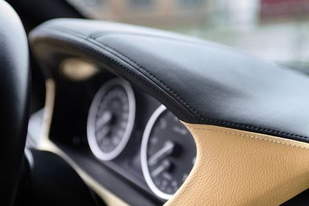 Speedometer and tachometer on dashboard of an luxury car closeup, covered with natural beige and black stitched leather. Stockfoto