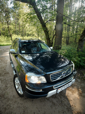 GRODNO, BELARUS - MAY 2015: Volvo XC90 4.4 v8 1st generation restyling 4WD SUV test drive in spring forest country road wide shot side vertical view with sunflares in Grodno Belarus