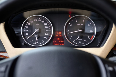 Multifunctional panel of luxury car with speedometer tachometer indicators and part of steering wheel out of focus closeup. Stok Fotoğraf