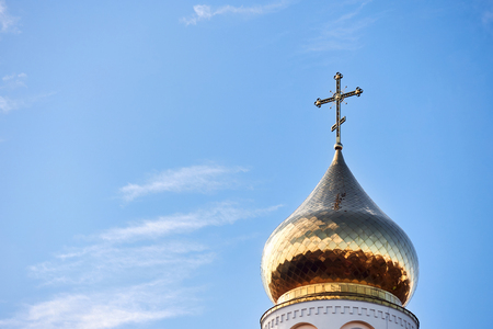 Golden dome and cross of Church of the Beheading of St. John the Baptist  in European city Grodno or Hrodna Belarus on blue sky background with cirrus clouds with copy space.