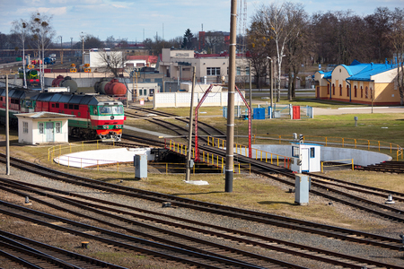 Diesel locomotive at entrance to railway turntable in railway depot on sunny spring day.