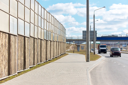Sound absorbing panels along freeway in city. Concept of protecting residential buildings from noise pollution using sound insulating panels.