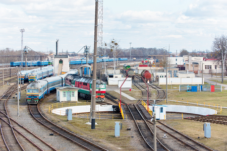 Diesel locomotives and carriages stand in depot near railway turntable. Stock Photo