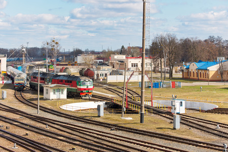 Diesel locomotive and train at entrance fork of railway turntable in railway depot on sunny spring day.