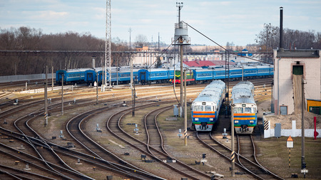 Diesel locomotives and carriages stand in depot with lots of rail forks and rails in sunny spring day.