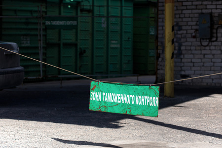 Green old rusty customs area sign at entrance to customs clearance with the inscription in Russian with freight railcar at background. Russian translation: Customs control zone. Stok Fotoğraf