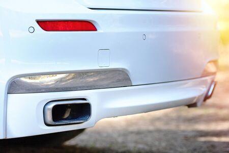 Enfoque selectivo en el parachoques del tubo de escape del sensor de estacionamiento en la parte trasera del parachoques de automóvil lujoso blanco de cerca en la luz borrosa con el fondo de la llamarada del sol.
