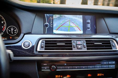 Innenraum des Premium-Autos mit Rückfahrkamera dynamischer Trajektorie-Wendelinien und Parkassistent. Fahrerassistenzsystem zum Parken. Helfen Sie mit, Optionen in Luxusautos zu unterstützen.